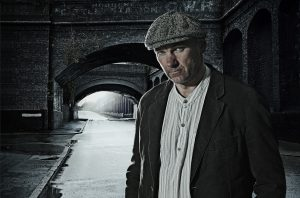 Portrait of man in peaked cap and Edwardian style clothes standing in front of a Victorian brick viaduct. The background is dark, wet and deserted, a working class Edwardian/Victorian Street scene.