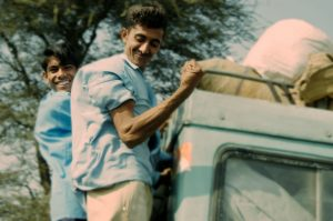 Image of two indian boys in blue shirts hanging off the back of a light green land Rover one of them flexing his muscles. On the way to work