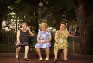 Three elderly ladies, sitting on green bench, resting in the park, each seemingly wrapped up in their own thoughts.
