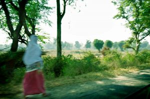 Image of blurred Indian woman walking alongside country road, India