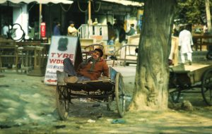 An Indian man asleep in cart wearing brown top and blue trousers and green scarf, Delhi, India