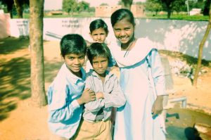 Four Indian school children smiling at camera in school yard in the Indian countryside