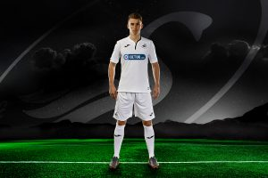 Tom Carroll. professional football player, Swansea City AFC, Midfielder wearing the home stip standing on football field with mountains and starry sky in the background and Swansea City logo floating in the sky