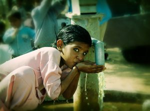 Indian school girl around ten years old wearing light pink top and trousers drinking water from water well in school yard, India