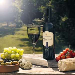 Bottle of red wine and glass with various cheeses, grapes, cherry tomatoes and olives on rustic wooden table in English garden