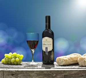 Bottle of red wine bottle and glass containing res wine on rustic wooden table with grapes and broken baguette against blue sky and hot sun flare and bokeh shapes in background.