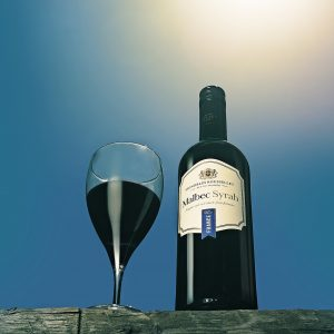 Bottle of red wine bottle and glass with wine against blue sky and hot sun flare