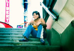 Young girl sitting on steps of subway wearing blue trousers and orange top, sporting self drawn tattoos with her thumb up